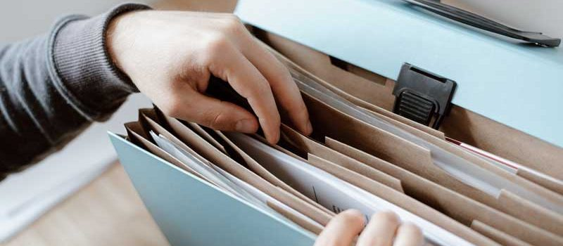 Person choosing documents from folders.