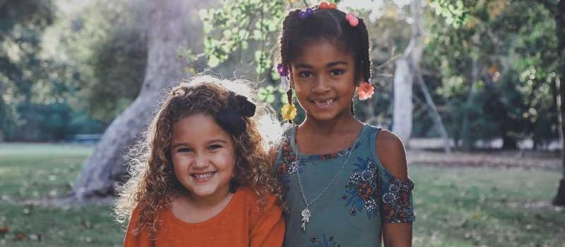 Two young girls who are friends, smiling.