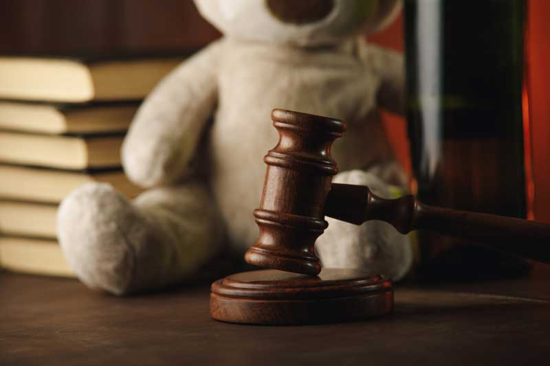judge's desk with gavel and teddy bear.