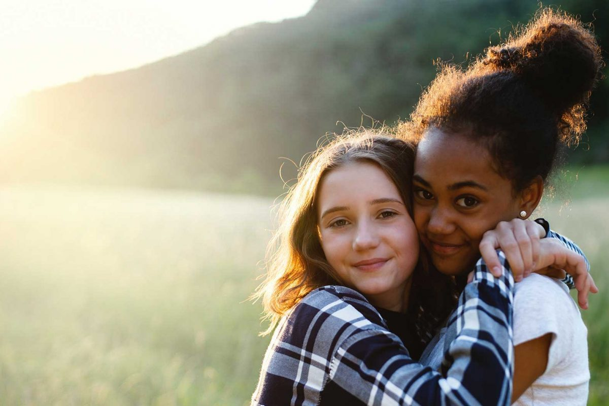 two foster sisters hugging in a field at sunrise.