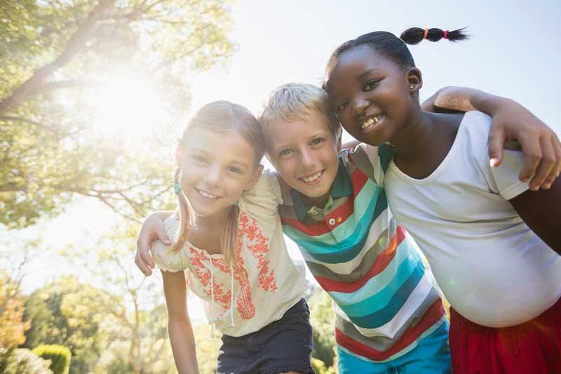 Group of children smiling outside.
