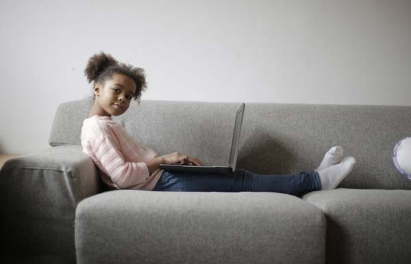 Young girl with laptop on couch.
